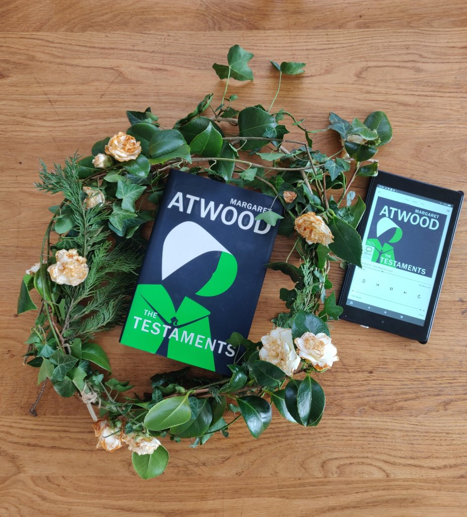 Image of a hardback copy of the Treatments, by Margaret Atwood, in a wreath and a kindle places next to it with the audio version of the same book.