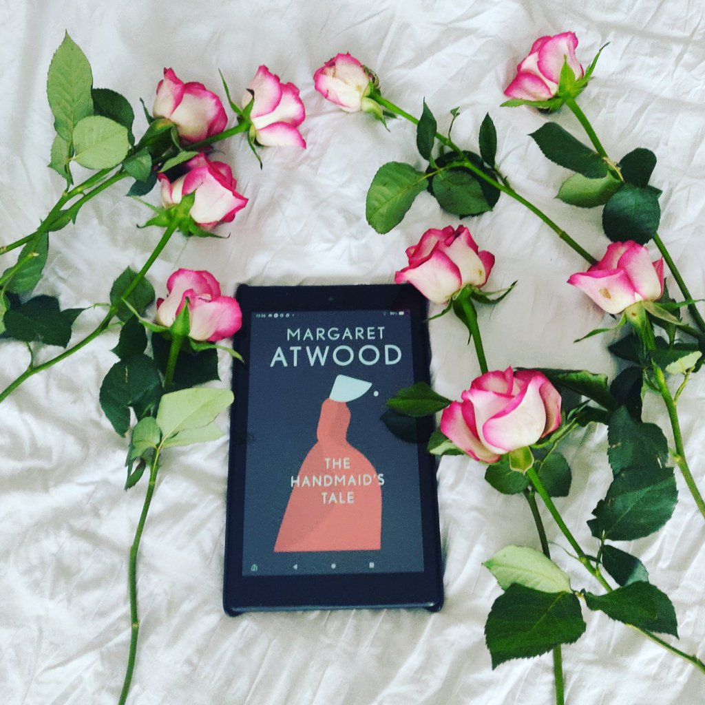 Image of a kindle devise with the Handmaid's Tale book cover, surrounded by pink roses on a bed.