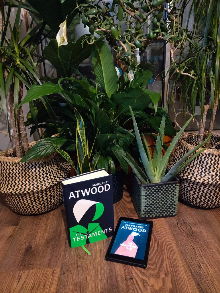 Image of the hardback copy of the Testaments and a kindle displaying the cover of The Handmaid's Tale, in front of some house plants.