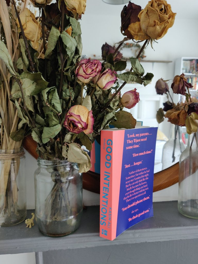 Copy of 'Good Intentions' by Kasim Ali on a fire place surrounded by dried roses.